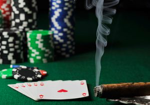 playing cards, chips and a cigar on a poker table
