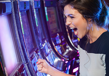 woman yelling in excitement in front of slot machine