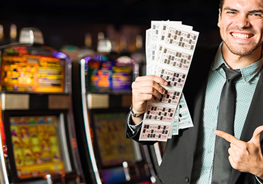 man holding and pointing at cards from slot machine