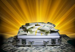 metal briefcase with bundles of cash around it