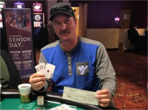 Man holding check and cards at poker table