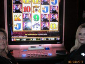 two women sitting at a slot machine