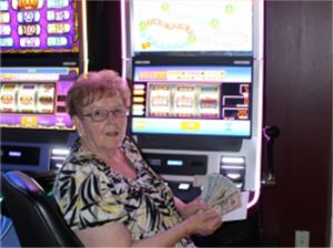 Woman holding money and sitting in front of slot machine