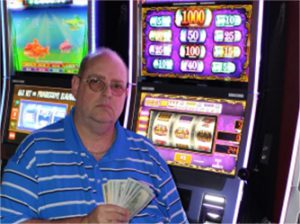 Man holding money and sitting in front of slot machine