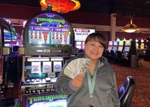 Female holding cash in front of Triple Diamond slot machine