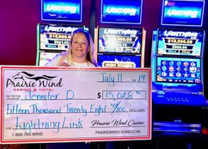 Woman holding large check for $15,028 in front of Lightning slot machine