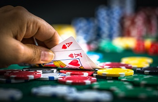 Person putting cards on a table covered in poker chips